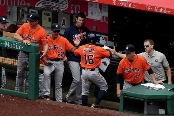 ANAHEIM, CA - MAY 29:  Tony Kemp #16 of the Houston Astros is congratulated by Trey Hillman #22 and A.J. Hinch #14  in the dugout after scoring on a single by Jose Altuve during the fifth inning of a baseball game against the Los Angeles Angels of Anaheim on May 29, 2016 in Anaheim, California.
