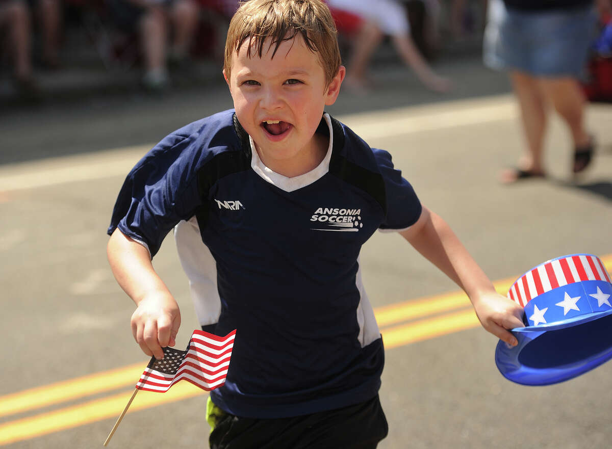 Andrew Endres, 9, of Ansonia, marching with the Ansonia Soccer League, runs to hand a flag to policeman during the Memorial Day parade on Main Street in Ansonia, Conn. on Sunday, May 29, 2016.