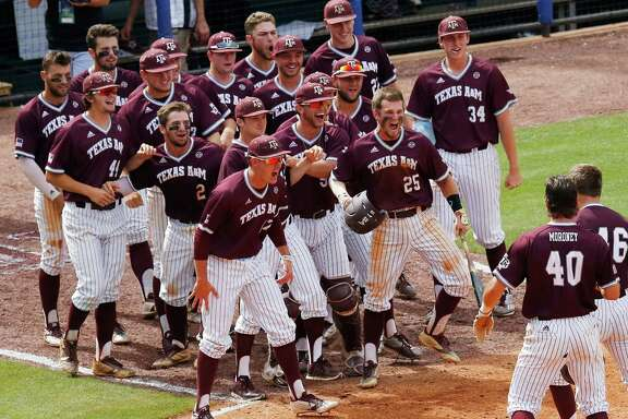 Texas A&M's Walker Pennington, lower right, is welcomed by teammates after Pennington hit a grand slam during the eighth inning of a Southeastern Conference NCAA college baseball tournament game against Mississippi at the Hoover Met, Saturday, May 28, 2016, in Hoover, Ala. (AP Photo/Brynn Anderson)