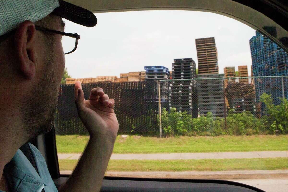Hunter Cox, an investigator working with the Texas Retailers Association drives by a wooden and plastic pallet shredding plant in Houston looking for stolen plastic pallets.