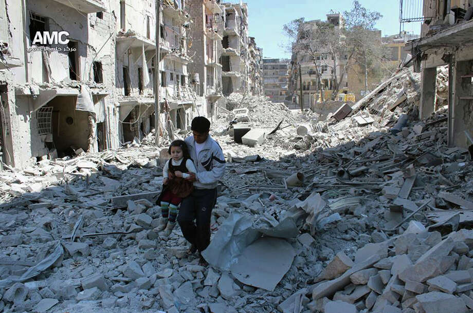 In This April 21, 2014, file photo, provided by the anti-government activist group Aleppo Media Center (AMC), which has been authenticated based on its contents and other AP reporting, shows a Syrian man holding a girl as he stands on the rubble of houses that were destroyed by Syrian government forces air strikes in Aleppo, Syria. Islamic State militants entered a Syrian opposition stronghold in the country's north on Saturday, clashing with rebels on the edges of the town as the extremist group built on its most significant advance near the Turkish border in two years, Syrian opposition groups and IS media said. (AP Photo/Aleppo Media Center AMC, File) Photo: Uncredited / Aleppo Media Center AMC