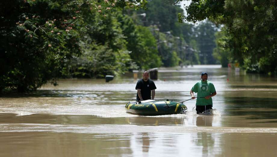 Thomas Wirtjes, left, and Tad Gibson, right, use a rubber boat on Hamblen Road, to bring back supplies to their homes surrounded by flood waters in the Forest Cove neighborhood, south of Kingwood, where flood waters from the San Jacinto Rivers reached levels not seen since 1994, Sunday, May 29, 2016, in Humble. Photo: Karen Warren, Houston Chronicle / © 2016 Houston Chronicle