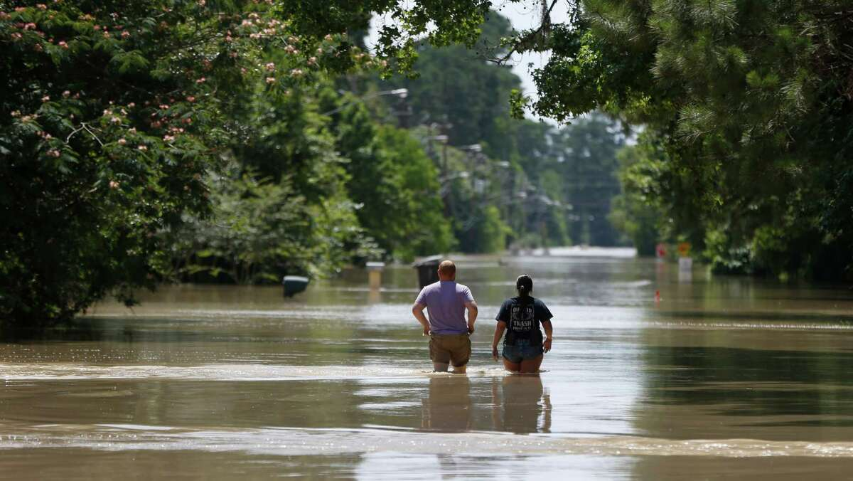 Residents walk through flood waters on Hamblen Road in the Forest Cove neighborhood, south of Kingwood, where flood waters from the San Jacinto Rivers reached levels not seen since 1994, Sunday, May 29, 2016, in Humble.