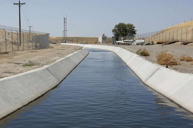 FILE - In this Tuesday, July 21, 2015 file photo, water flows down a diversion canal operated by the Byron-Bethany Irrigation District, that is drawn out of a channel leading to to the William O. Banks pumping plant, near Byron, Calif. Water regulators have recommended dismissing a historic $1.4 million fine issued at the height of California�s drought against a group of Central Valley farmers. The State Water Resources Control Board on Thursday, May 26, 2016, said its prosecutors failed to prove the case against Byron-Bethany Irrigation District. (AP Photo/Rich Pedroncelli, File)