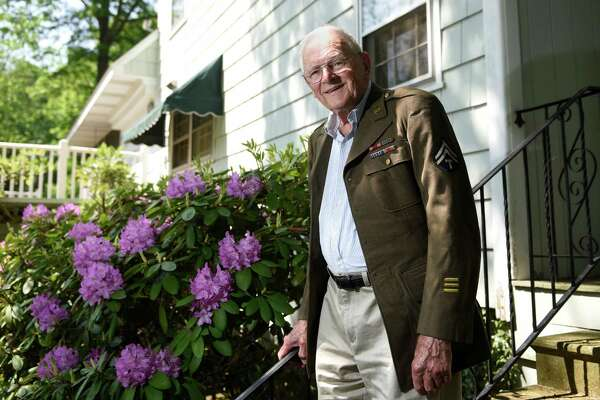 WWII veteran James MacKay poses wearing his original wartime jacket on the porch outside his home in Greenwich, Conn. Wednesday, May 26, 2016. MacKay, 95, served in the U.S. Army and was recently flown by the Honor Flight Network with 63 other veterans to Washington, D.C. to participate in an honor ceremony and tour the memorials around the captial.