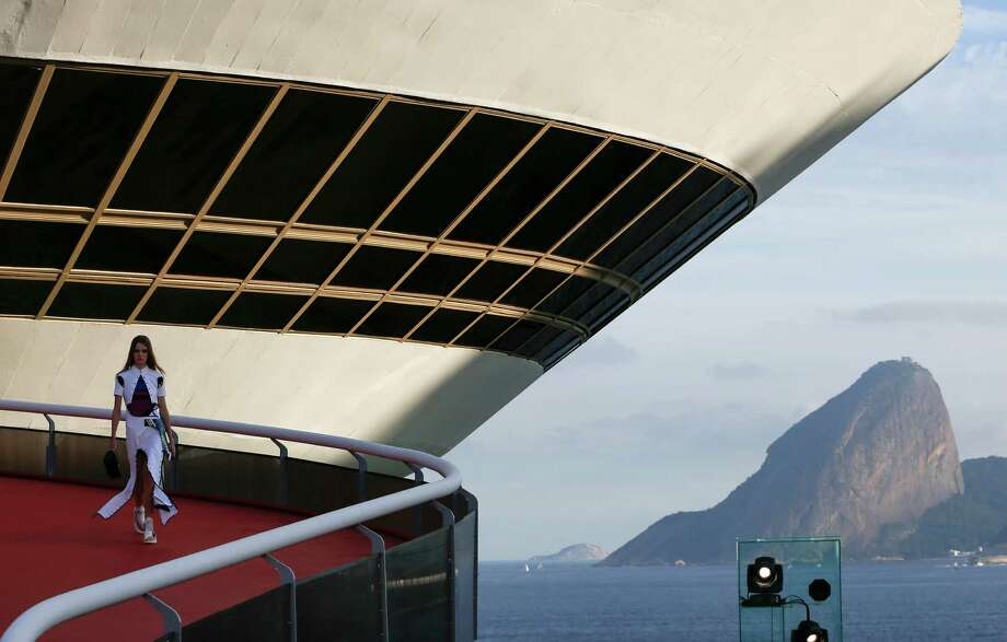 A model walks down a ramp of the Contemporary Art Museum wearing a creation from the Louis Vuitton Crusie 2017 collection, in Niteroi, Brazil, Saturday, May 28, 2016. The elite of the fashion world flocked to Brazil, defying an outbreak of the Zika virus, an economic meltdown and the profound political crisis afflicting the country to attend a runway show Saturday by revered French label. The iconic Sugarloaf Mountain is pictured in the background on right. (AP Photo/Leo Correa) ORG XMIT: XLC113 Photo: Leo Correa / AP