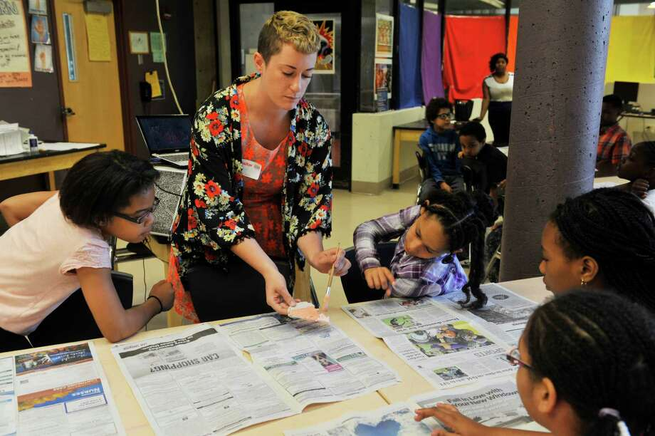 Artist Jillian Hirsch shows students at Arbor Hill Elementary School how to apply glaze to their clay butterflies they made on Monday, May 23, 2016, in Albany, N.Y.  Hirsch designed, with community input, the mosaic that the butterflies will be used to make.   (Paul Buckowski / Times Union) Photo: PAUL BUCKOWSKI / 40036684A