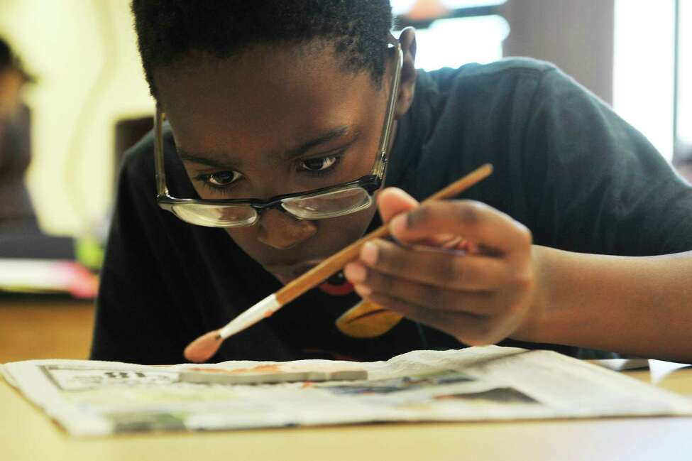 Arbor Hill Elementary School studentQuincy Hippolyte, 10, applies glaze to a clay butterfly he made on Monday, May 23, 2016, in Albany, N.Y. The butterflies the students made will be part of a large mosaic. (Paul Buckowski / Times Union)