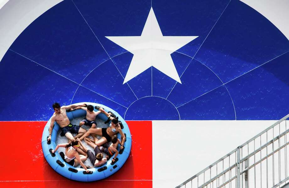 Visitors to Typhoon Texas water park slide down a Texas flag-thremed water slide during the grand opening of the park on Saturday, May 28, 2016, in Katy. Photo: Brett Coomer, Houston Chronicle / Mandatory Credit