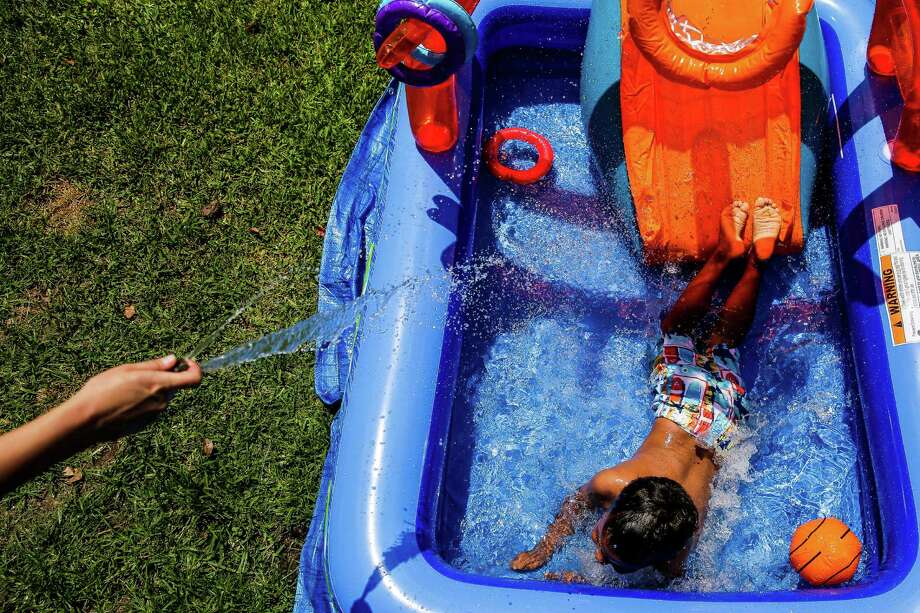 Carol Jeffery sprays her four-year-old foster child with the hose as they set up a new pool in their back yard Monday, May 23, 2016 in Houston. The foster parents, Jeffery and Angela Sugarek, welcomed their two foster kids, brothers ages 3 and 4, back into their home almost two months after Child Protective Services took the kids away after they reported the youngest child was being abused by an older brother. Photo: Michael Ciaglo, Houston Chronicle / Mandatory Credit