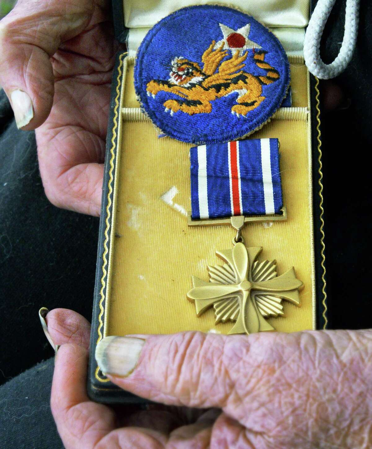 World War II veteran of the 14th Army Air Force Jack Gordon, 95, holds his Distinguished Flying Cross and Flying Tigers patch at his rural home Thursday May 19, 2016 in Broome, NY. Gordon was a senior navigator on a C47 flying over