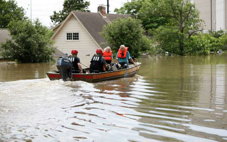 A couple are rescued Sunday from their flooded home in Humble's Northshire neighborhood.