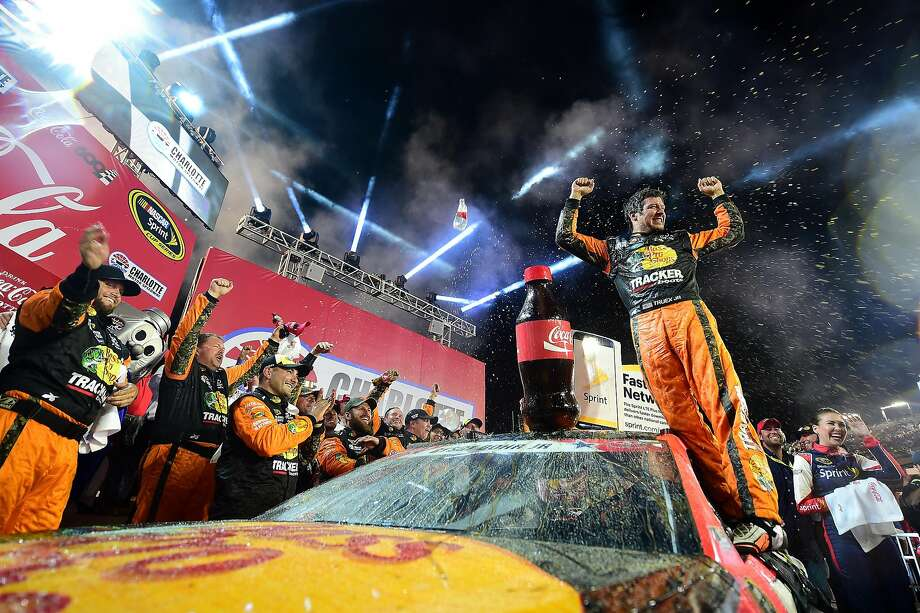 Martin Truex Jr., driver of the No. 78 Bass Pro Shops/Tracker Toyota, celebrates after his easy victory in the NASCAR Sprint Cup Series Coca-Cola 600 at Charlotte (N.C.) Motor Speedway. Photo: Jared C. Tilton