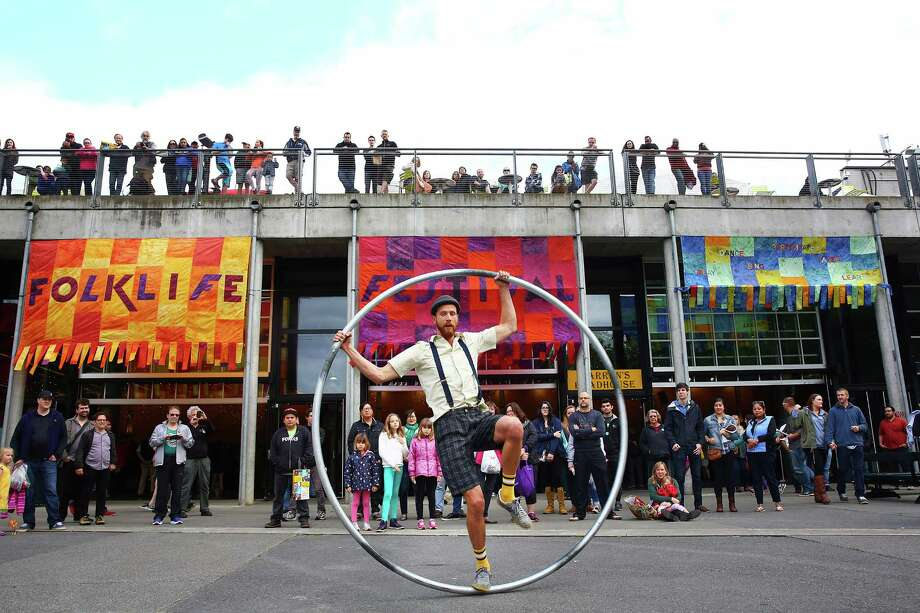 Spectators watch as Ty Vennewitz spins on his Cyr wheel during the 2016 Northwest Folklife Festival at Seattle Center, May 29, 2016. Photo: GENNA MARTIN, SEATTLEPI.COM / SEATTLEPI.COM
