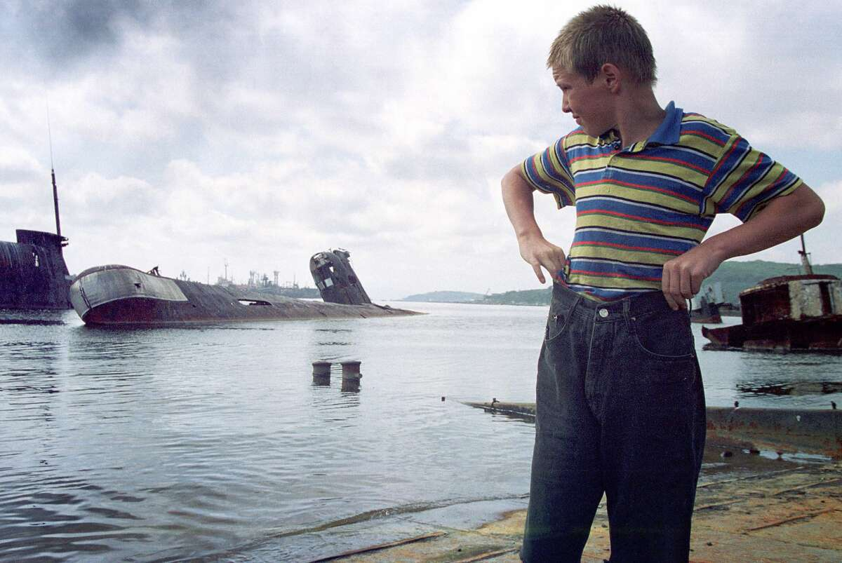"""A youngster plays near an area where old Russian submarines are retired September 12, 2000 in Vladivostok, Russia. The area is known as the """"Submarine cemetery"""" and the Russian government says it does not have enough money to dismantle the old vessels. (Photo by Oleg Nikishin/Newsmakers)"""