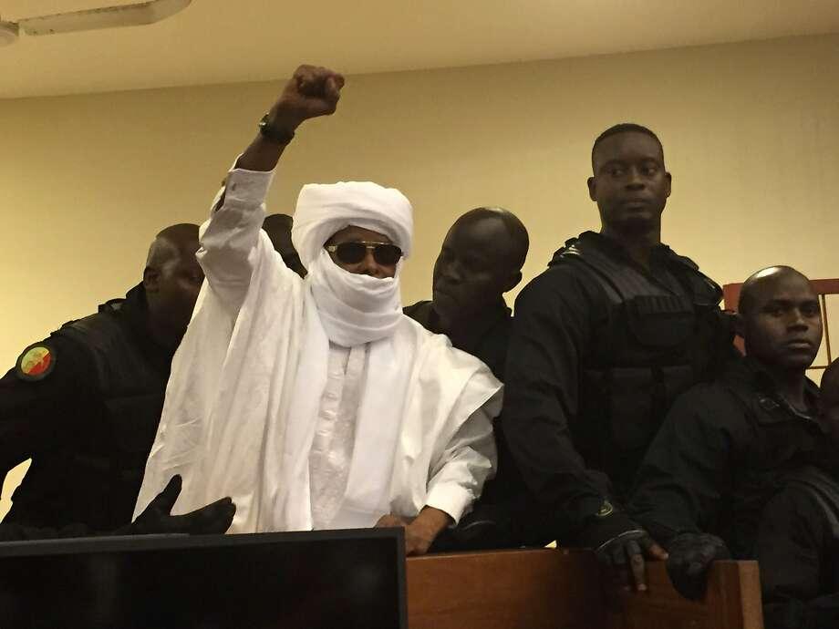 Hissene Habre, former dictator of Chad, raises his fist during court proceedings in Dakar, Senegal. Photo: Carley Petesch, Associated Press
