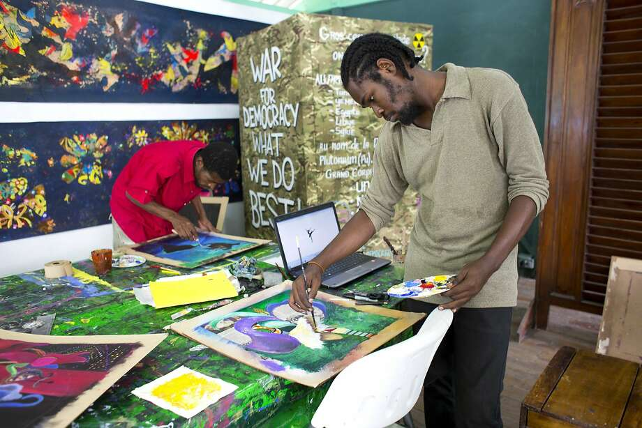 Art student Rubens Corneille (right) paints during class at the Centre d'Art in Port-au-Prince, Haiti. Photo: Dieu Nalio Chery, Associated Press