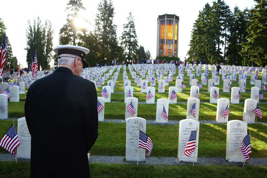Vietnam U.S. Navy veteran Joe Clyde looks out over the WWII section of graves in the veterans' section of Evergreen-Washelli cemetery, Monday, May 30, 2016, in Seattle.  Several dozen volunteers placed flags at each of the veteran graves for Memorial Day. Photo: SEATTLEPI.COM / SEATTLEPI.COM