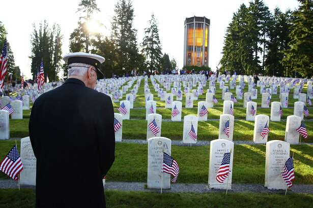 Vietnam U.S. Navy veteran Joe Clyde looks out over the WWII section of graves in the veterans' section of Evergreen-Washelli cemetery, Monday, May 30, 2016, in Seattle.  Several dozen volunteers placed flags at each of the veteran graves for Memorial Day.