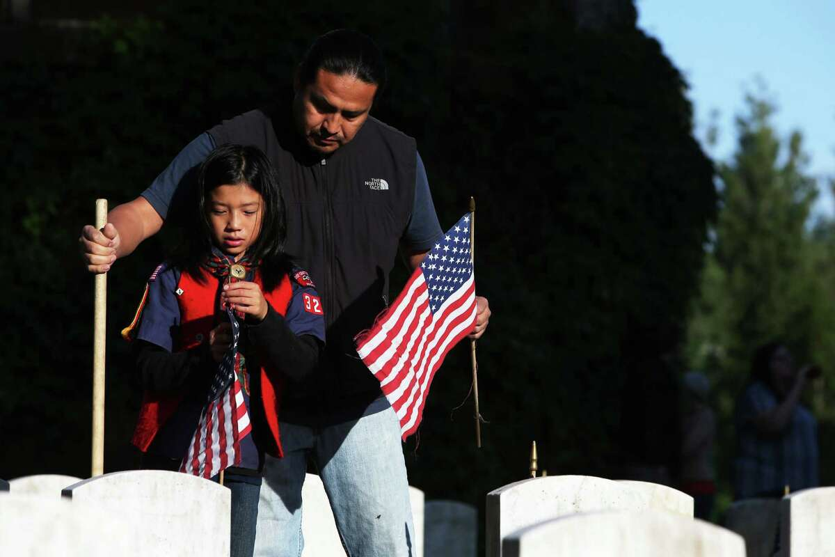 Shondee Seaton and his son Kai, 9, place flags at gravestones in the veterans' section of Evergreen-Washelli cemetery on Memorial Day, Monday, May 30, 2016, in Seattle. Several dozen volunteers placed flags at the 5,000 veteran graves.