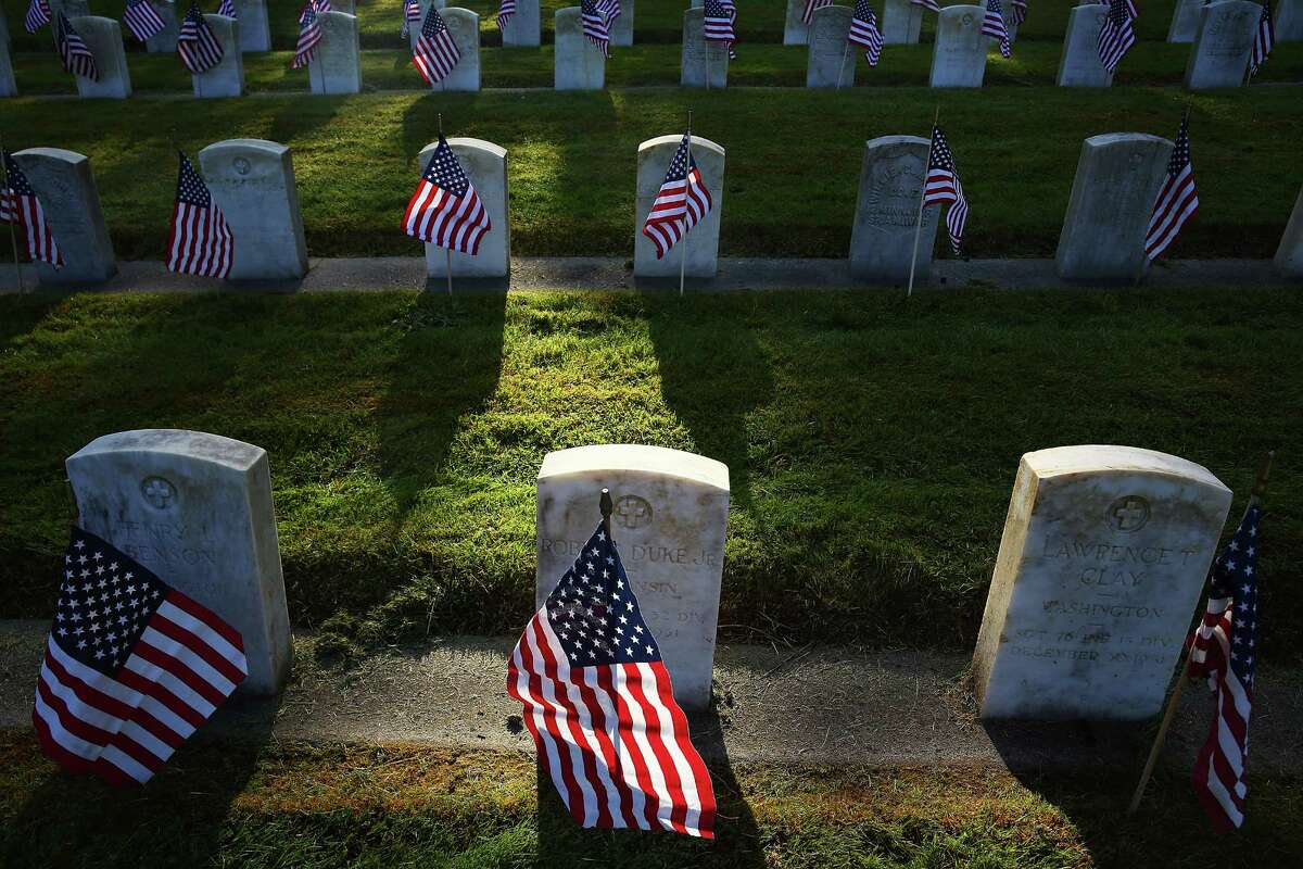 Several dozen volunteers placed flags at each of the 5,000 graves in the veterans' section of Evergreen-Washelli cemetery on Memorial Day, Monday, May 30, 2016, in Seattle.