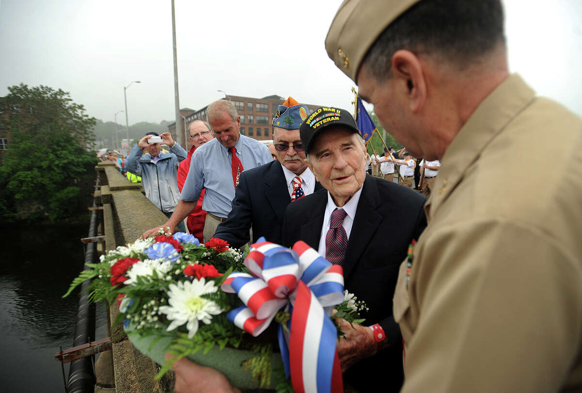 Shelton/Derby Memorial Day parade Grand Marshal Dennis Salzer, right, of Shelton, assists World War 2 veteran Roy Glover, 94, of Shelton, throw a wreath into the Housatonic River during the Memorial Day ceremony on the Derby-Shelton Bridge on Monday, May 30, 2016.
