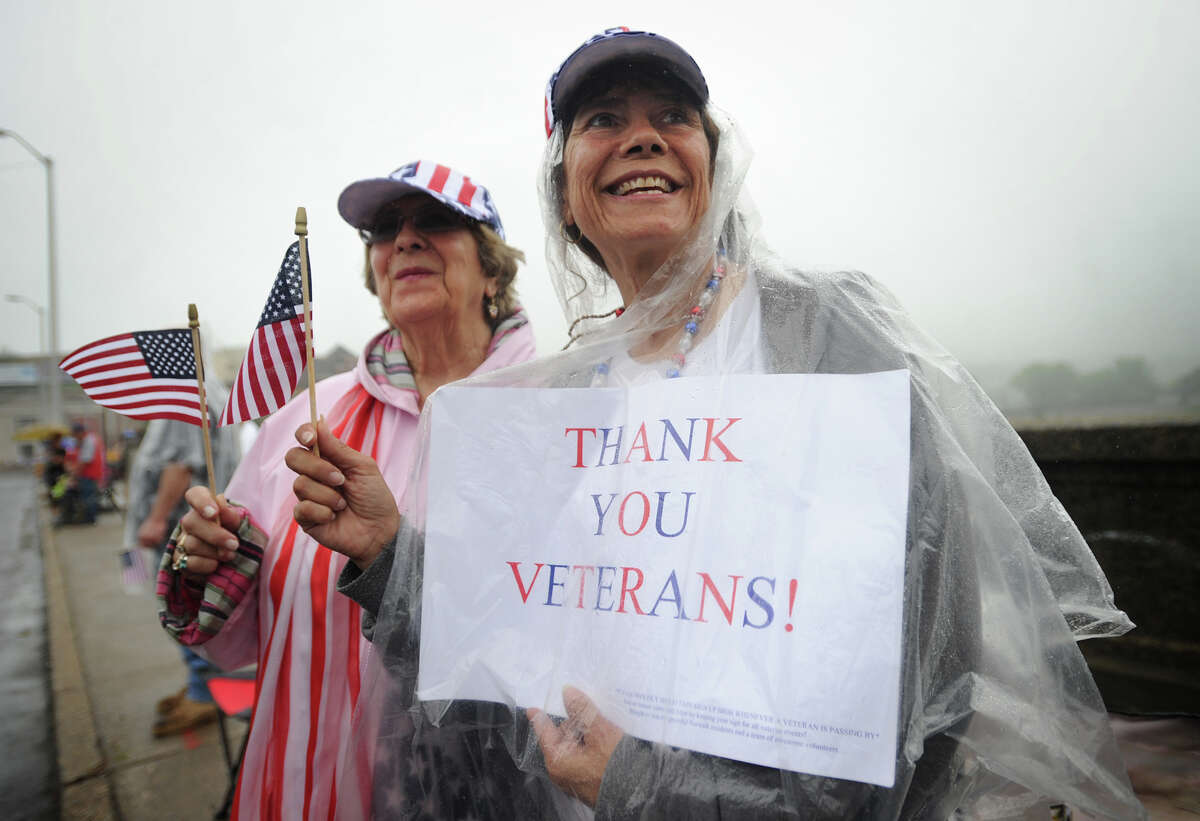Ginny Colabella, left, of Norwalk, and her daughter Tracy Fascio, of Shelton, keep dry as they show their support for veterans during the Shelton/Derby Memorial Day parade on Monday, May 30, 2016.