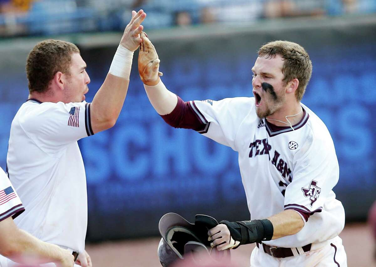 Texas A&M's Austin Homan, right, high-fives teammate Michael Barash, left, after scoring against Florida in the seventh inning of the Southeastern Conference NCAA college baseball championship game Sunday, May 29, 2016, in Hoover, Ala. (AP Photo/Brynn Anderson)