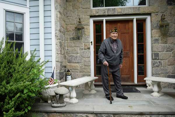 WWII veteran Fred Intrieri stands outside his home on Intrieri Lane in the Cos Cob section of Greenwich, Conn. Tuesday, May 24, 2016. Intrieri entered the U.S. Army in 1943 and served in the Eighth Air Force and 90th Infantry Division, including action in the famous Battle of the Bulge, before being honorably discharged in 1946.