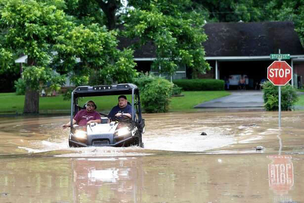 Men in a four-wheeler drive through 21-inch deep flood water at Greenwood and Strange Drive Monday, May 30, 2016, in Richmond.