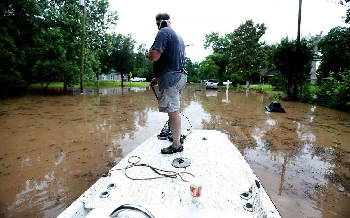 Jim Klentzman maneuvers his boat through 21-inch deep floodwaters near his home at Greenwood and Strange Drive Monday, May 30, 2016, in Richmond.