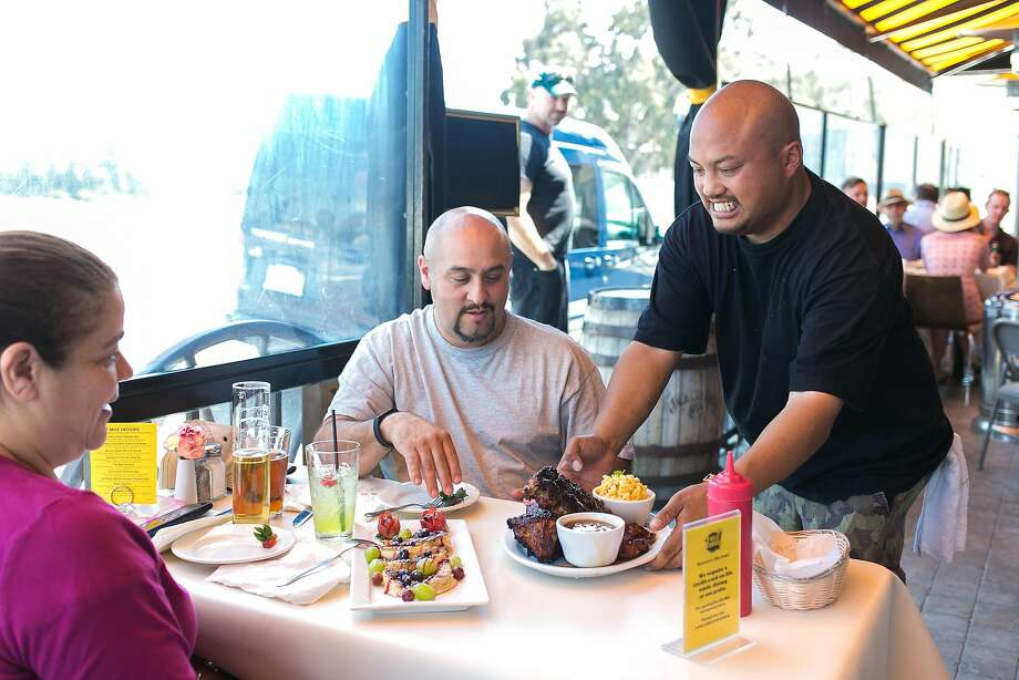 Chris Nobida serves up ribs to Anthony and Emilia Quinones at 7 Mile House in Brisbane. Photo: Jen Fedrizzi, Special To The Chronicle