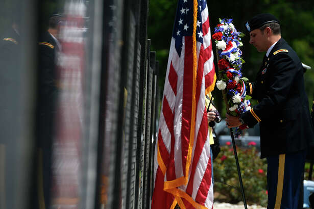 Lt. Col. Brad Bane, commander of the 842nd Transportation Battalion at the Port of Beaumont, lays a wreath in front of the Veterans Honor Wall during a Memorial Day ceremony at Forest Lawn Memorial Park in Beaumont on Monday.  Photo taken Monday 5/30/16 Ryan Pelham/The Enterprise