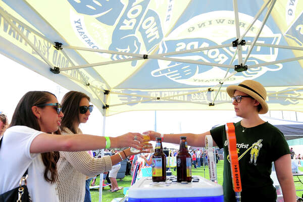 Right, Emily Sauter, of Two Roads Brewery in Stratford, gives samples to Alyssa Mantilla, of New Haven, and her friend Devon McKenna, of Fairfield, during the Harbor Brew Fest in Bridgeport. Two Roads will be one of the vendors at the Brews on Bedford festival in Stamford next month.