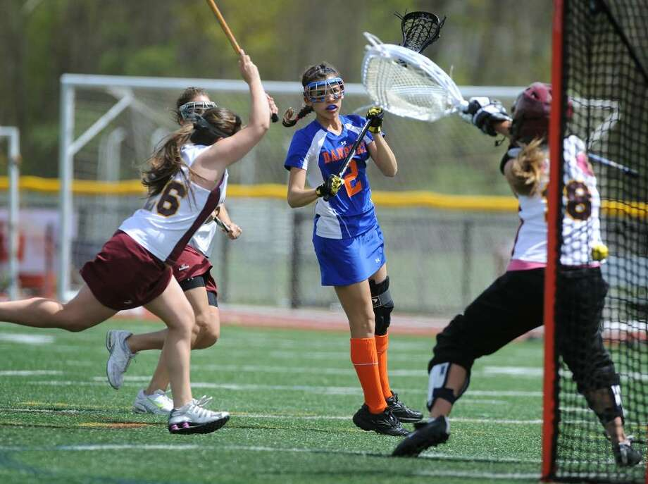 Danbury's Gina Newsome, center, fires a shot past St. Joseph goalie Gabby Depa during Tuesday's girls lacrosse matchup at St. Joseph High School in Trumbull. Photo: Brian A. Pounds / Connecticut Post