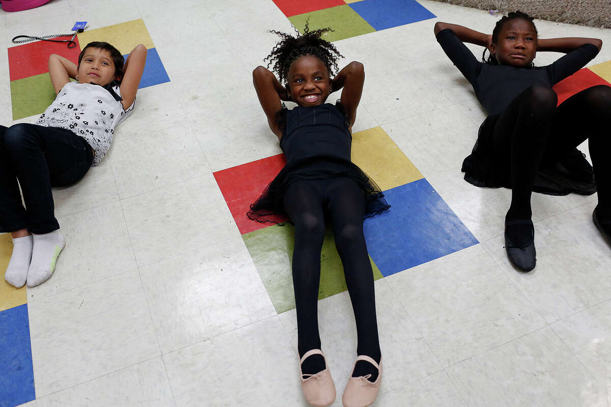 Alexia Ibarra, 9, Jaida Prude, 8, and Janae Howell, 9, do crunches during the warm up for their ballet class at the Boys and Girls Clubs of San Antonio Eastside Branch on Oct. 2, 2015.