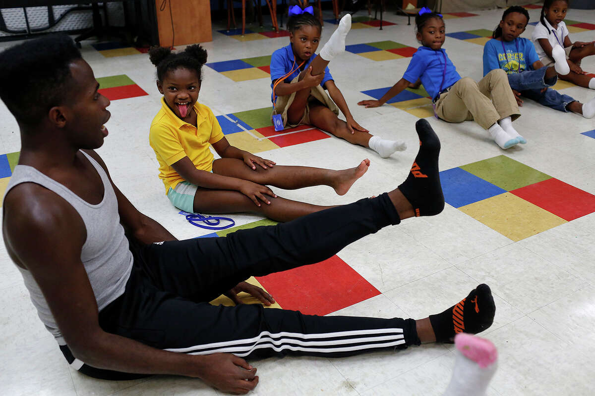 Christopher McDaniel, a Demi Soloist with Ballet San Antonio, leads students including Kenya Christopher, 8, (tongue out) in stretches during their ballet class at the Boys and Girls Clubs of San Antonio Eastside Branch on Oct. 2, 2015.