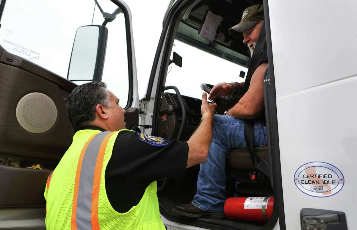 Javier Flores, left, a member of the County of Bexar Environmental Law Enforcement team, talks with truck driver Buster Hutchins of Dallas, to let drivers know about the anti-idling restrictions, on Tuesday, May 17, 2016, at the Flying J Travel Plaza on I-10 east.