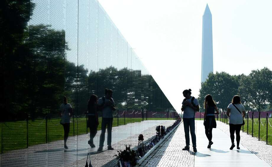 The Washington Monument is seen in the background as people visit the Vietnam Memorial in Washington, Friday, May 27, 2016, on the stat of the Memorial Day weekend. (AP Photo/Susan Walsh) Photo: Susan Walsh, Associated Press / Copyright 2016 The Associated Press. All rights reserved. This material may not be published, broadcast, rewritten or redistribu