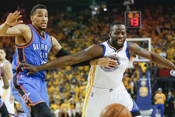 Golden State Warriors' Draymond Green and Oklahoma City Thunders' Andre Roberson fight for a loose ball in the first quarter during Game 7 of the NBA Western Conference Finals at Oracle Arena on Monday, May 30, 2016 in Oakland, Calif.