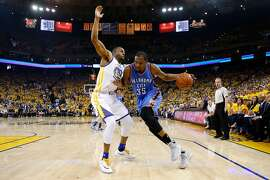 OAKLAND, CA - MAY 30:  Kevin Durant #35 of the Oklahoma City Thunder drives with the ball against Andre Iguodala #9 of the Golden State Warriors in Game Seven of the Western Conference Finals during the 2016 NBA Playoffs at ORACLE Arena on May 30, 2016 in Oakland, California. NOTE TO USER: User expressly acknowledges and agrees that, by downloading and or using this photograph, User is consenting to the terms and conditions of the Getty Images License Agreement.  (Photo by Ezra Shaw/Getty Images)