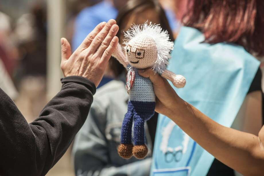 Tony Wang of Oakland gets high fives with his sock puppet doll from fellow supporters of democratic presidential candidate, Senator Bernie Sanders as the wait in line for a campaign rally at Frank Ogawa Plaza in Oakland, California, USA 30 May 2016. (Peter DaSilva/Special to The Chronicle) Photo: Peter DaSilva, Special To The Chronicle