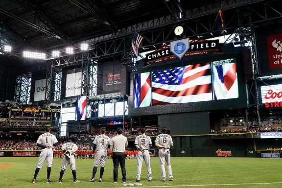 Astros players Carlos Correa, Jose Altuve, George Springer, Marwin Gonzalez and Jake Marisnick join a moment of silence in honor of Memorial Day before Monday's game against Arizona at Chase Field in Phoenix.