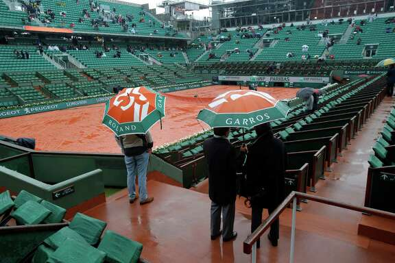 A few spectators survey the scene at center court of the French Open on Monday before organizers postponed all of the day's matches.