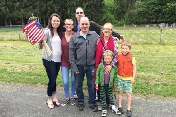 From left, Claire Filler, Jaclyn Gold, Allan Filler, Mark Menard, Sylva Menard, Avi Menard and Ezra Menard visit the Temple Beth El Cemetery in Troy to place American flags on at the headstones of veterans as part of tradition they're involved in. (Submitted photo)