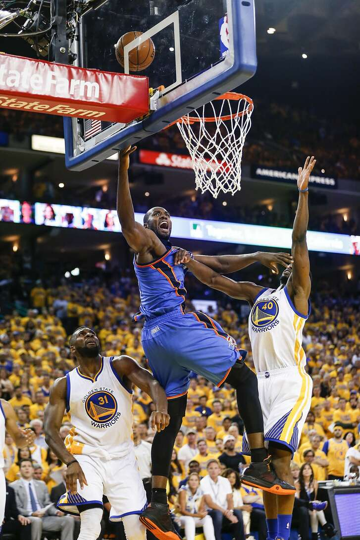 Oklahoma City Thunders' Serge Ibaka goes up for a shot against Golden State Warriors' Festus Ezeli and Harrison Barnes in the third quarterduring Game 7 of the NBA Western Conference Finals at Oracle Arena on Monday, May 30, 2016 in Oakland, Calif.