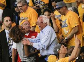 Sen. Bernie Sanders talks with a fan during Game 7 of the NBA Western Conference Finals at Oracle Arena on Monday, May 30, 2016 in Oakland, Calif.