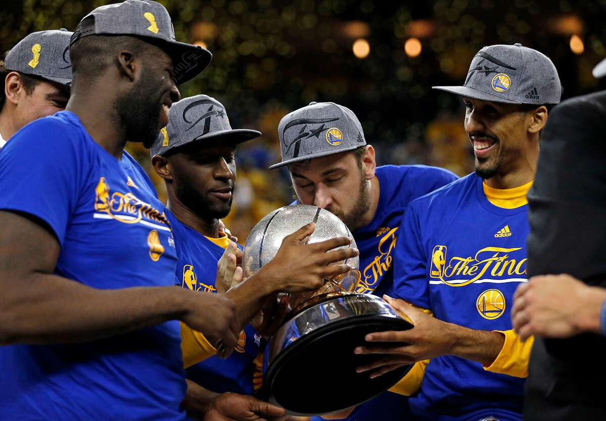 Golden State Warriors' Andrew Bogut kisses Western Conference Championship trophy as Draymond Green, Ian Clark and Shaun Livingston watch after 96-88 win over Oklahoma City Thunder in Game 7 of NBA Playoffs' Western Conference finals at Oracle Arena in Oakland, Calif., on Monday, May 30, 2016.