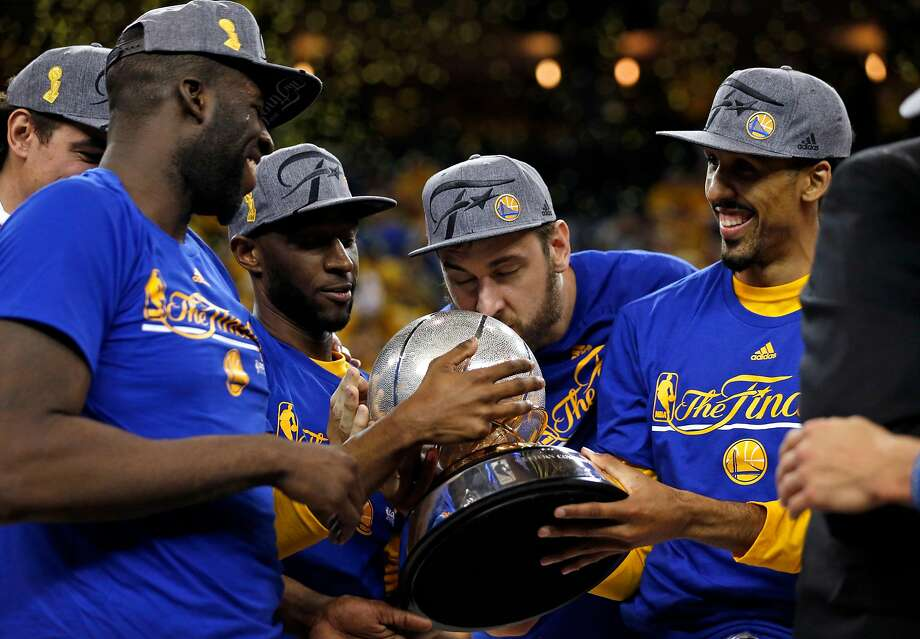 Golden State Warriors' Andrew Bogut kisses Western Conference Championship trophy as Draymond Green, Ian Clark and Shaun Livingston watch after 96-88 win over Oklahoma City Thunder in Game 7 of NBA Playoffs' Western Conference finals at Oracle Arena in Oakland, Calif., on Monday, May 30, 2016. Photo: Scott Strazzante, The Chronicle