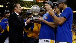 Golden State Warriors' legend Rick Barry hands Western Conference Championship trophy to Klay Thompson after 96-88 win over Oklahoma City Thunder in Game 7 of NBA Playoffs' Western Conference finals at Oracle Arena in Oakland, Calif., on Monday, May 30, 2016.